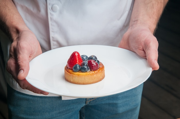 Restaurant chef holding plate with sweet dessert
