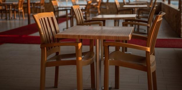 저녁에 황량한 식당에 대해 ''코로나바이러스로 인해 식당 폐쇄'' 안내문. 고품질 사진