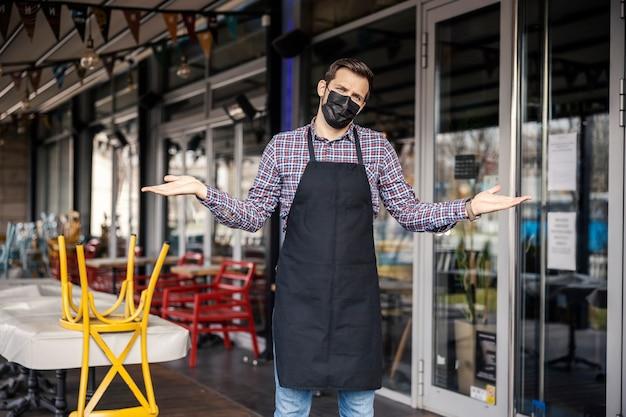 Covid-19로 인해 레스토랑이 문을 닫았습니다. 불만을 보여주는 마스크와 웨이터의 초상화