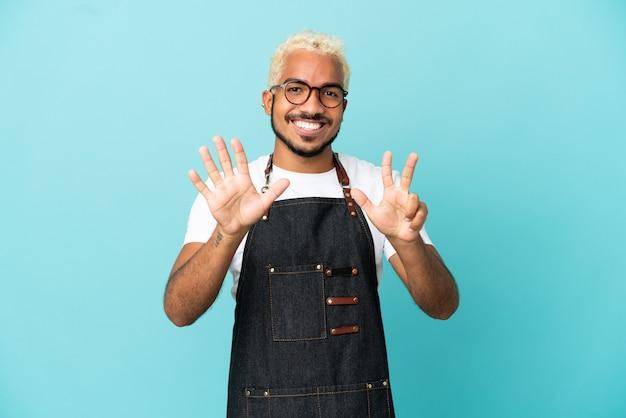 Ресторан колумбийский официант мужчина изолирован на синем фоне, считая восемь пальцами