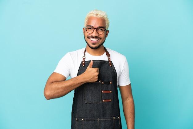 레스토랑 콜롬비아 웨이터 남자는 파란색 배경에 고립 제스처를 엄지손가락을 포기