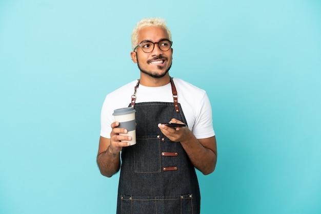 Ресторан колумбийский официант, изолированный на синем фоне, держит кофе на вынос и мобильный, думая о чем-то