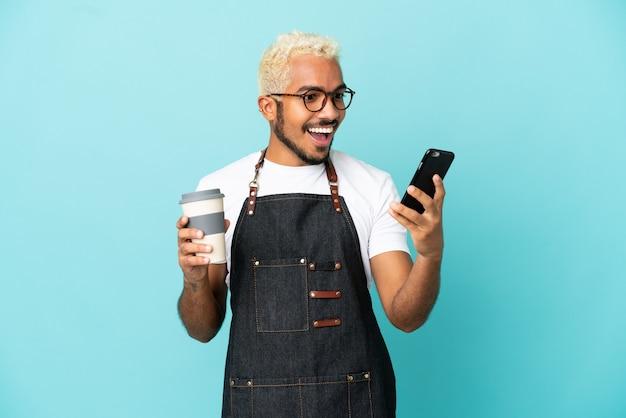 Ресторан колумбийский официант, изолированные на синем фоне, держит кофе на вынос и мобильный