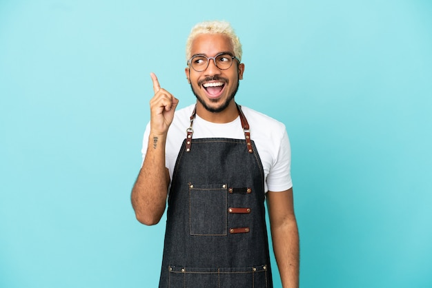Ресторан колумбийский официант изолирован на синем фоне, намереваясь реализовать решение, подняв палец вверх