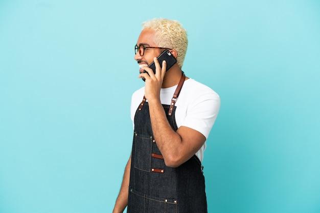 Ресторан колумбийский официант, изолированный на синем фоне, разговаривает с кем-то по мобильному телефону