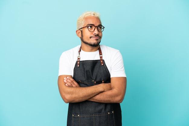 Ресторан колумбийский официант мужчина изолирован на синем фоне, делая жест сомнения, поднимая плечи