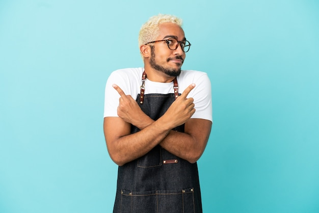 Ресторан колумбийский официант, изолированные на синем фоне, указывая на боковые стороны, сомневаясь