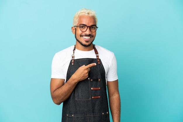 Ресторан колумбийский официант мужчина изолирован на синем фоне, указывая в сторону, чтобы представить продукт