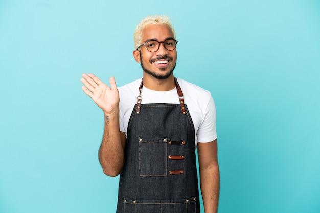 Ресторан колумбийский официант мужчина изолирован на синем фоне, салютуя рукой с счастливым выражением лица