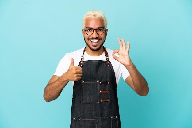 Ресторан колумбийский официант мужчина изолирован на синем фоне, показывая знак ок и жест пальца вверх