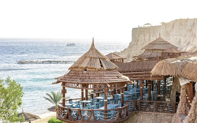A restaurant complex on the seashore among the rocks.