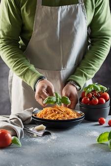 레스토랑 개념. 토마토와 바질로 이탈리아 스파게티를 요리하는 남자,