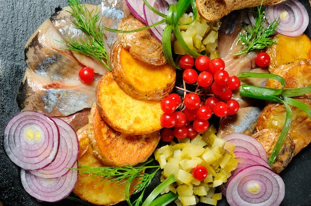 Restaurant dish - baked potatoes with onion rings and herring close-up