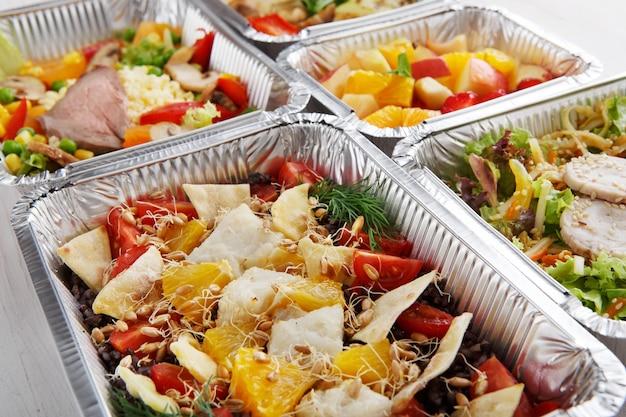 レストランの料理の配達。ホイルボックスに食べ物を持ち帰ります。タラの魚、小麦の芽、白い木でカリカリのトルティーヤの部分とサラダ