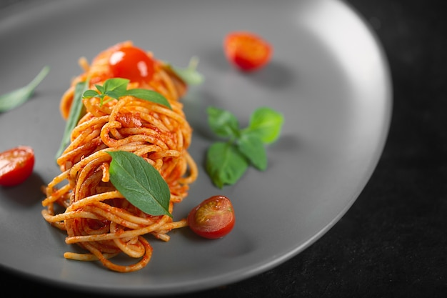 Restaurant dish prepared by the chef pasta in tomato sauce with cherry tomatoes and basil