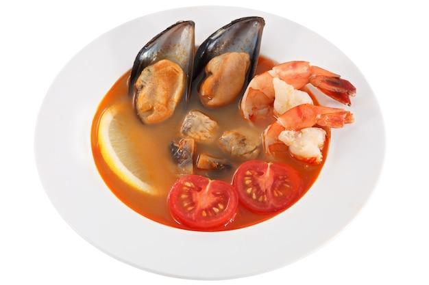 Блюдо ресторана, красный суп из морепродуктов и помидоры с мидиями и креветками, изолированными на белом фоне.