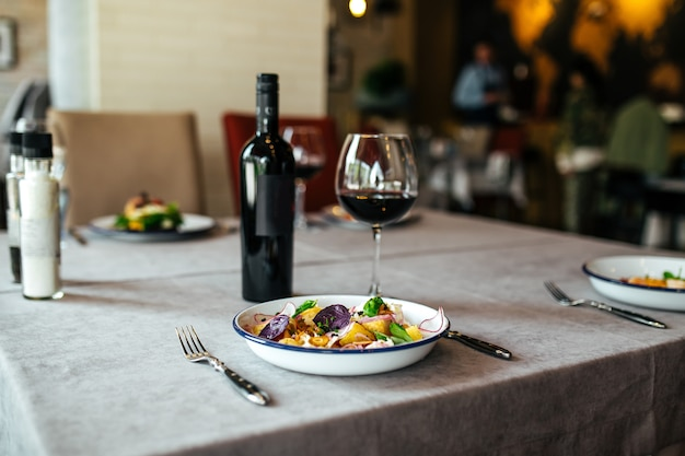 Restaurant dish served on the table with red wine