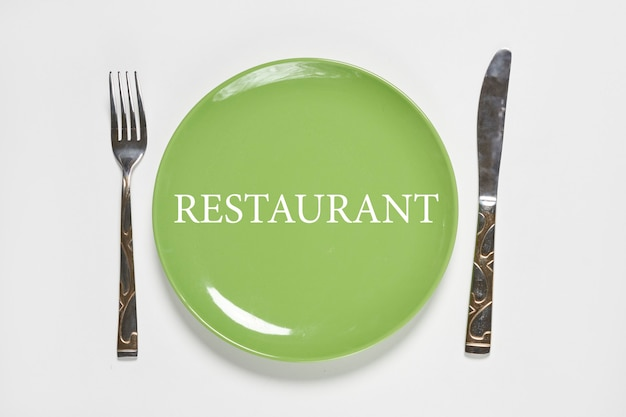 Restaurant eating items green plate and fork with kitchen knife on white background