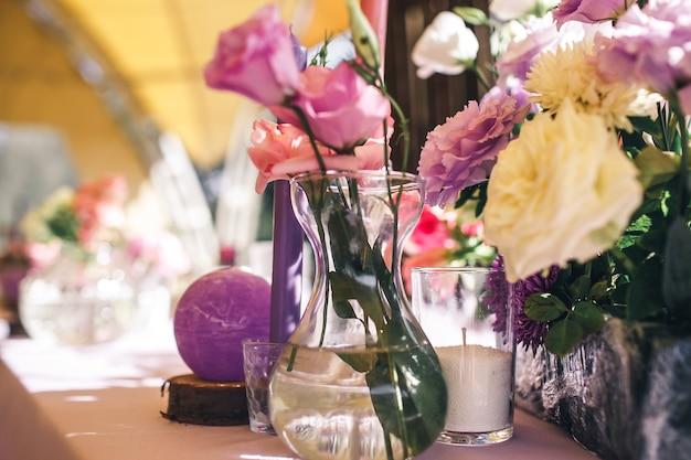 花とキャンドルでレストランのお祝いのテーブルの装飾