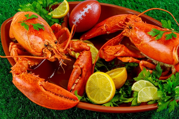 Restaurant food for american football game parry red lobsters on plate with ball