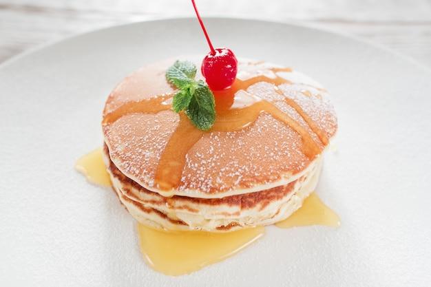 レストランの食べ物。甘いアメリカンパンケーキ。白いプレートの背景にチェリーと蜂蜜のクレープ。伝統的なアメリカ料理。