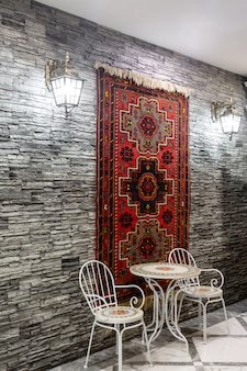 Restaurant hall with grey stone wall decorated with azerbaijani carpet