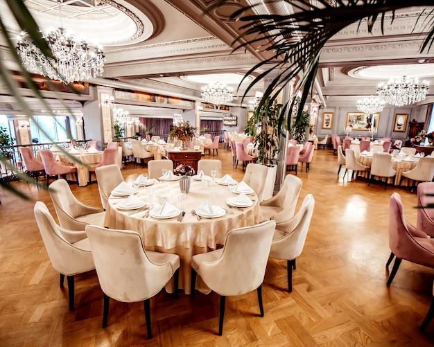 円形と正方形のテーブルと椅子と植物のあるレストランホール