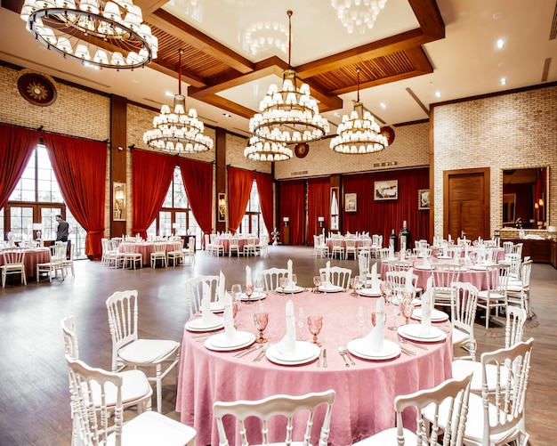 Restaurant hall with round tables, white napoleon chairs red curtains brick walls and chandeliers