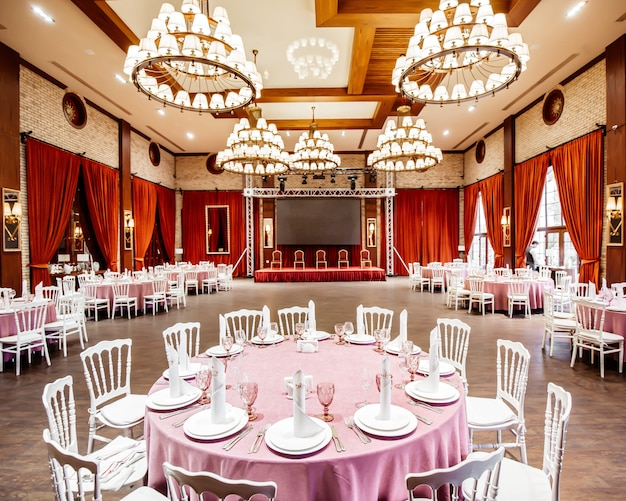 Restaurant hall with small stage monitor, red curtains, brick walls white napoleon chairs