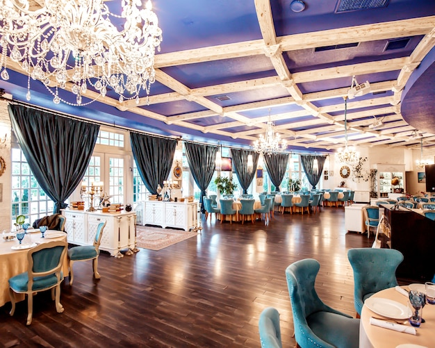 Restaurant hall with turquoise chairs, french windows navy coloured ceiling