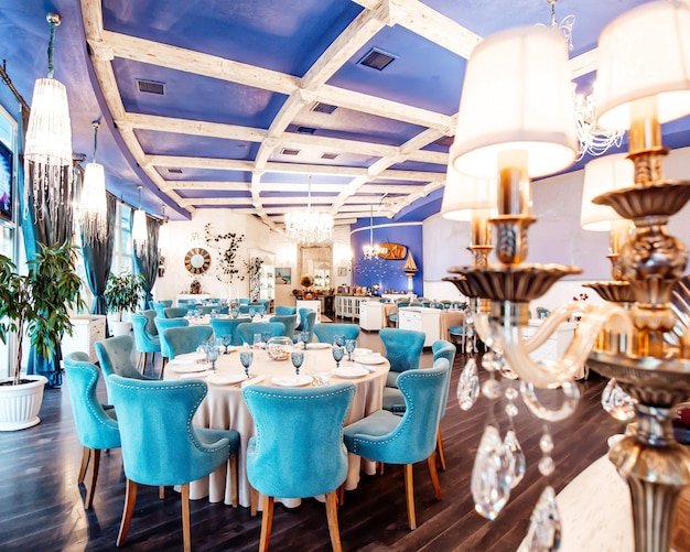ターコイズブルーの椅子、ネイビー色の天井、クラシックなシャンデリア、白い壁のあるレストランホール