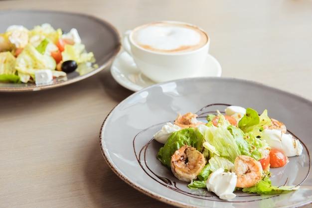 Ресторан здорового питания, салат, руккола с креветками и помидорами черри, покрытые пармезаном, крупным планом на тарелке