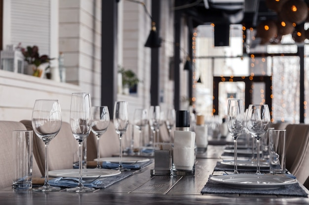 Restaurant interior, serving wine and water glasses, plates, forks and knives on textile napkins stand in a row on vintage gray wooden table