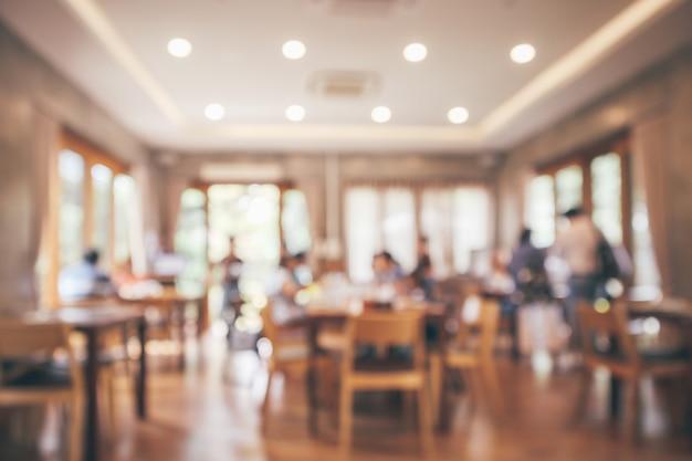 고객 및 나무 테이블 레스토랑 인테리어 bokeh 빛으로 추상적 인 배경을 흐리게