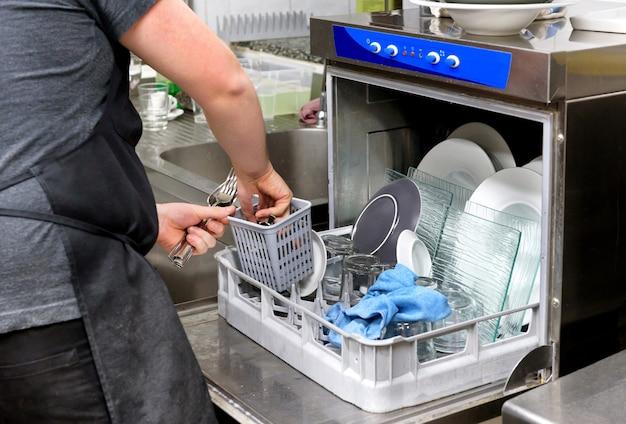 Работник кухни ресторана опорожняет посудомоечную машину, вынимая чистые столовые приборы из корзины крупным планом на руках
