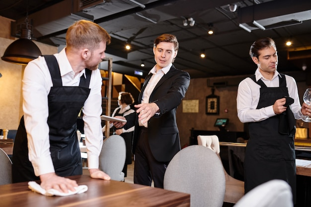 Restaurant manager giving task to waiter during cleanup