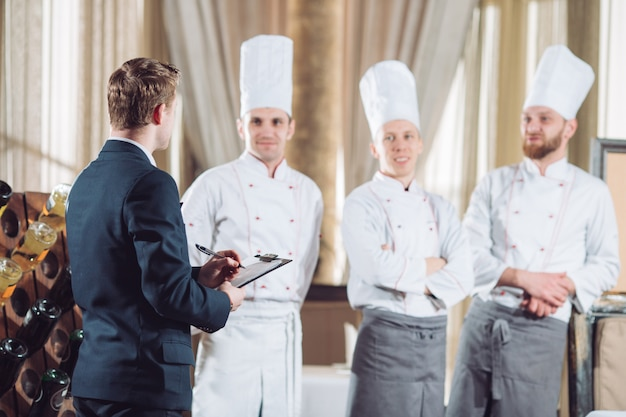 Restaurant manager and his staff in kitchen. interacting to head chef in commercial kitchen.