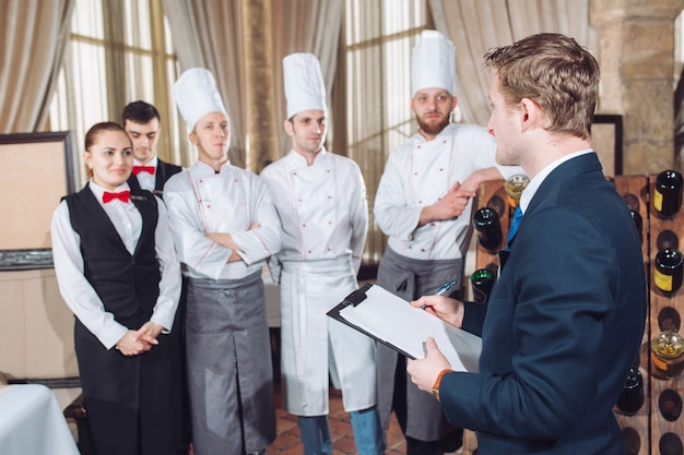 Restaurant manager and his staff in kitchen