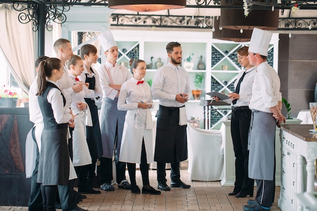 Restaurant manager and his staff in terrace, interacting to head chef in restaurant,