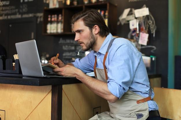 Менеджер ресторана работает на ноутбуке, подсчитывая прибыль.