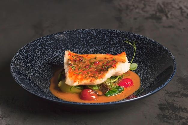 レストランのメニュー。ジューシーな焼き魚の切り身とチェリーグリーンとマイクログリーンの明るいオレンジソース