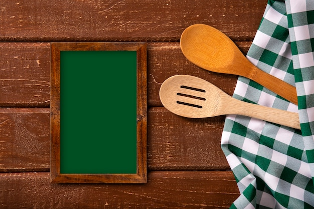 Restaurant menu. top view of chalkboard menu laying on the rustic wooden desk with spoons and green napkin.top view