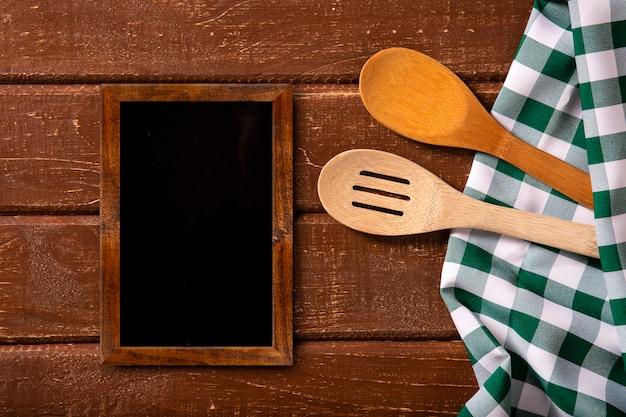 レストランメニュー。スプーンと緑のナプキンと素朴な木製の机の上に置く黒板メニューの上面図。上面図