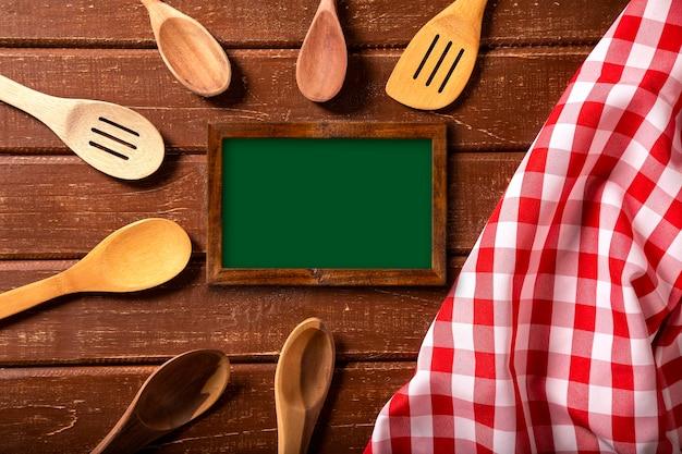 Меню ресторана. вид сверху меню на доске, лежащей на деревенском деревянном столе с ложками и красной салфеткой. вид сверху.