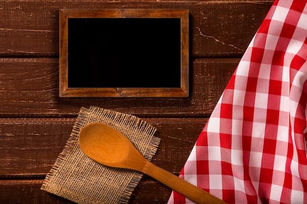 レストランメニュー。スプーンと赤いナプキンと素朴な木製の机の上に置く黒板メニューの上面図。上面図。