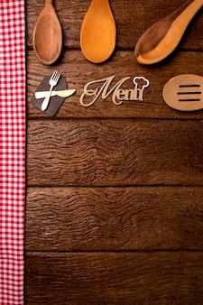 レストランメニュー。アクセサリー付きの素朴な木製の机の上に横たわる木板メニューの上面図。