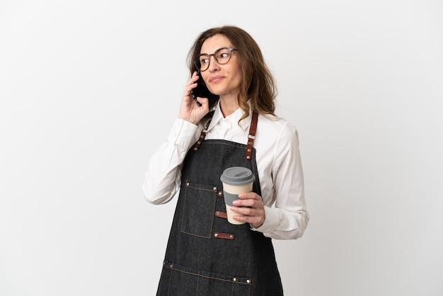 흰색 배경에 격리된 레스토랑 중년 웨이터 여성은 테이크아웃 커피와 모바일을 들고 있습니다.
