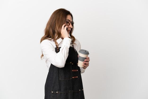 持ち帰り用のコーヒーと携帯電話を保持している白い背景で隔離のレストラン中年ウェイターの女性
