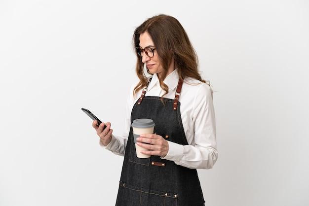 Ресторан средних лет официант женщина, изолированные на белом фоне, держа кофе на вынос и мобильный
