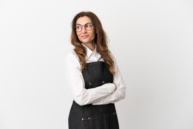 Ресторан среднего возраста официант женщина, изолированные на белом фоне со скрещенными руками и счастливыми